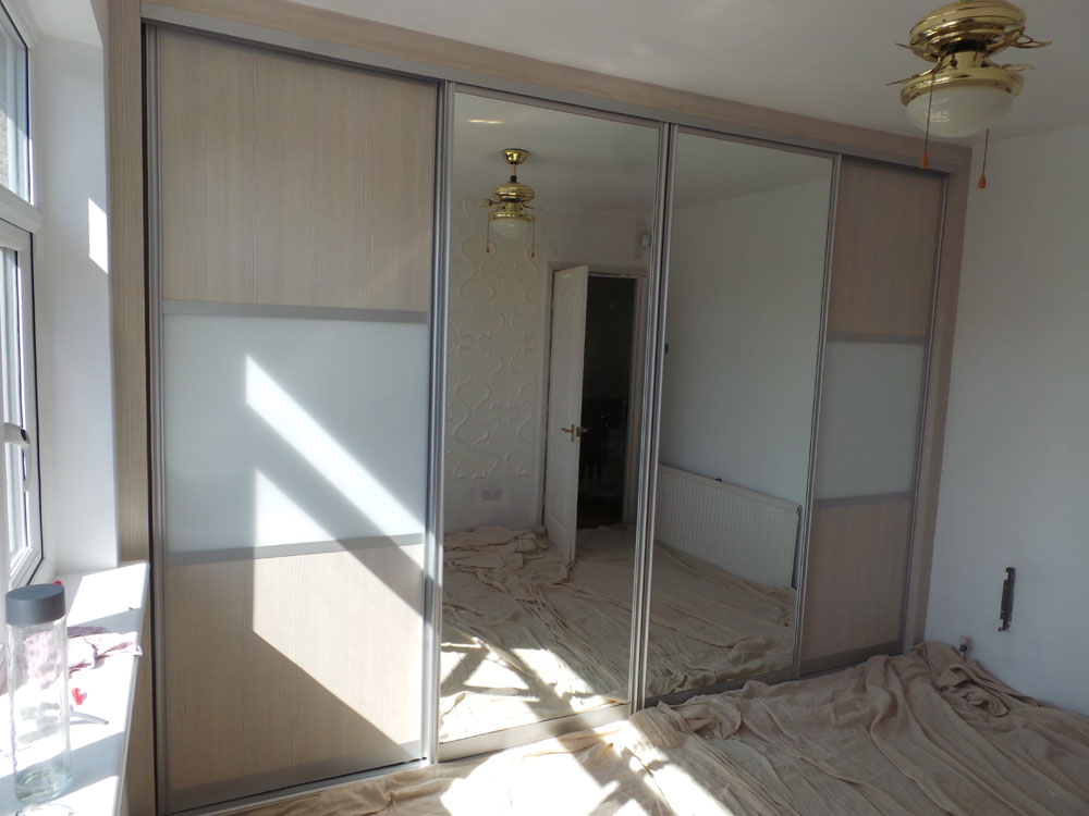 Fitted Sliding Doors Wardrobe with White Avola and White Glass doors combined with Mirrored Doors